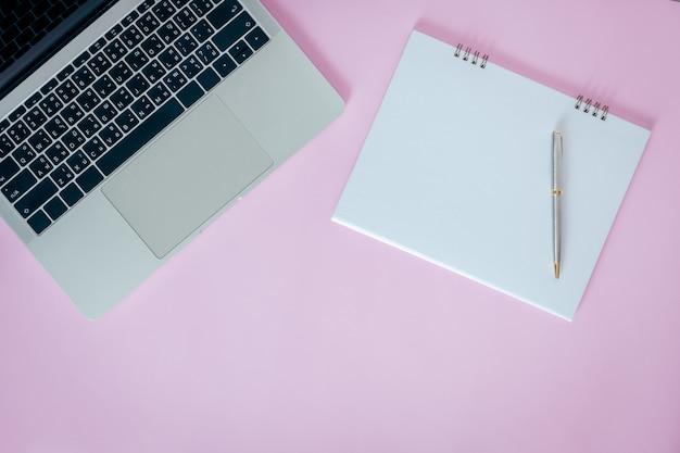 Cahier ouvert blanc avec ordinateur portable sur fond rose. pose à plat, vue de dessus