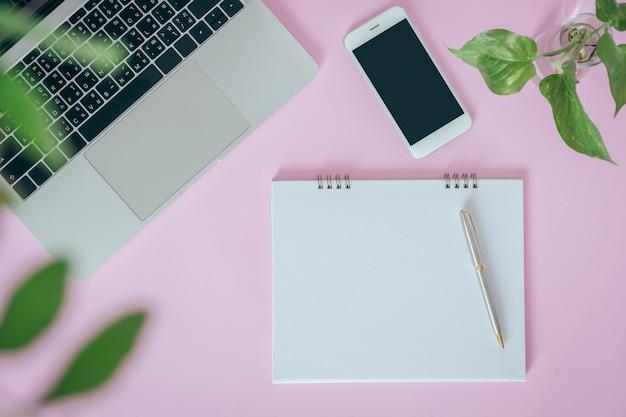 Cahier ouvert blanc avec ordinateur portable, smartphone sur fond rose. pose à plat, vue de dessus