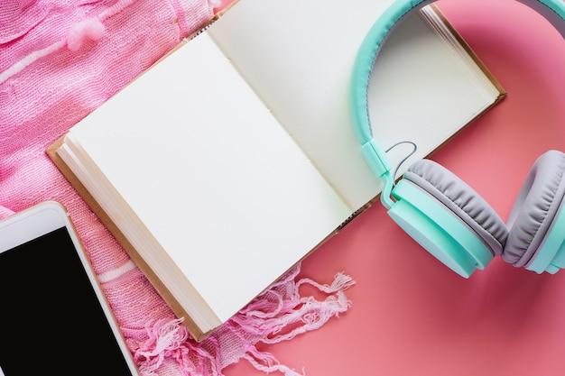 Cahier ouvert avec casque et smartphone sur écharpe pinky et fond rose