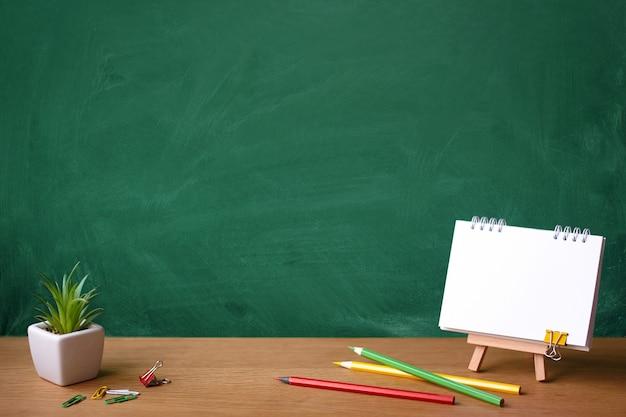 Cahier ouvert sur chevalet miniature, succulente dans une casserole et crayons de couleur sur le fond d'un tableau vert taché de craie, espace de copie