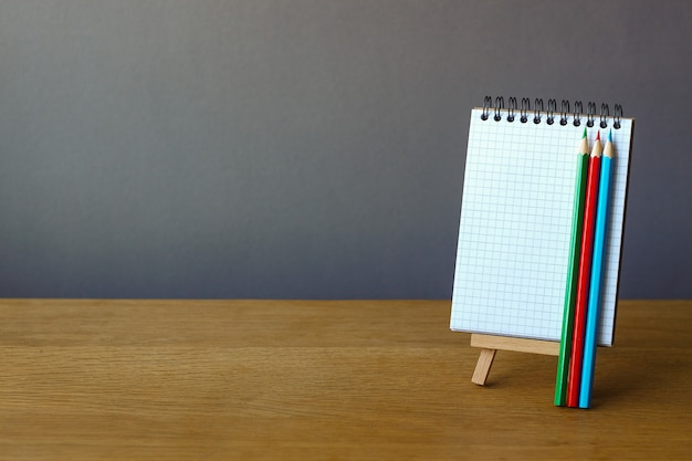 Cahier ouvert sur un chevalet miniature et trois crayons de couleur