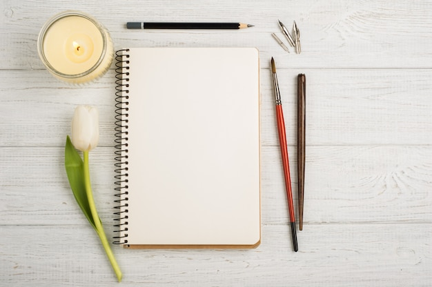 Cahier ouvert, crayon, bougie, pinceaux et tulipes