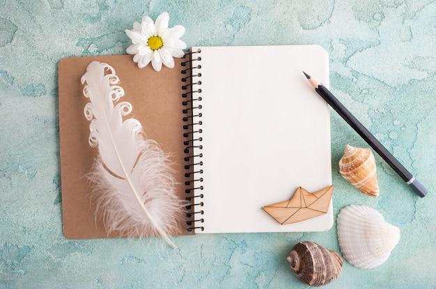 Cahier ouvert, crayon, coquillages, bateau en bois