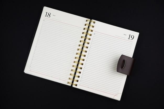 Cahier ouvert en cuir marron sur une surface noire