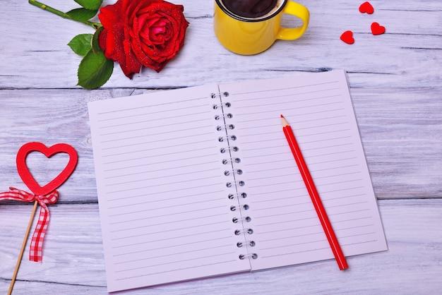 Cahier ouvert dans une rangée sur un fond en bois blanc