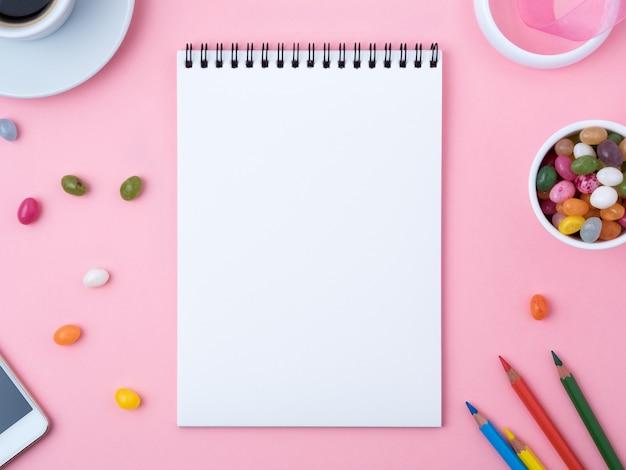 Cahier ouvert avec un drap blanc, du caramel, des sucettes, un crayon, une tasse de café