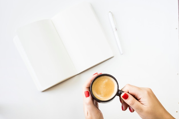 Un cahier ouvert avec des draps blancs à côté d'un stylo blanc et une tasse de café