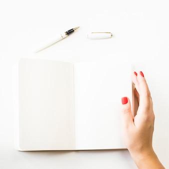 Cahier ouvert avec des draps blancs et une main féminine avec manucure rouge.