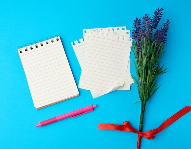 Cahier ouvert avec des feuilles blanches et un stylo en plastique rose sur une surface bleue