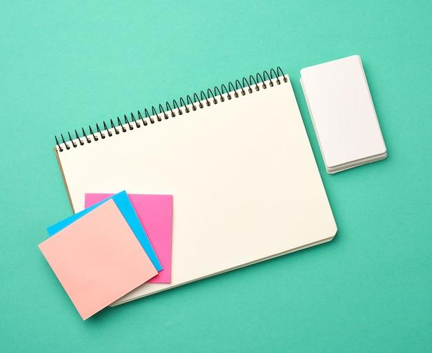 Cahier ouvert avec des feuilles blanches vierges, des autocollants de couleur et des cartes de visite rectangulaires sur fond vert