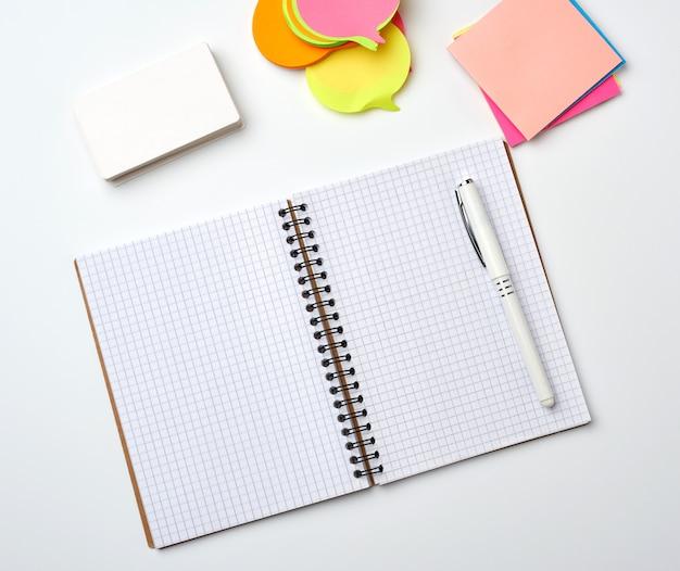 Cahier ouvert avec des feuilles blanches vierges, des autocollants de couleur et des cartes de visite rectangulaires