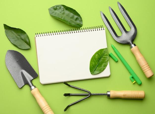 Cahier ouvert avec des feuilles blanches vierges et divers outils de jardinage avec des poignées en bois sur un mur vert, à plat, copiez l'espace