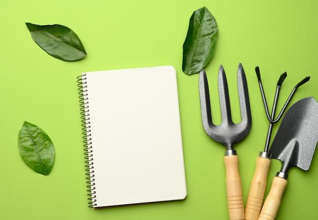 Cahier ouvert avec des feuilles blanches vierges et divers outils de jardinage avec des poignées en bois sur vert.
