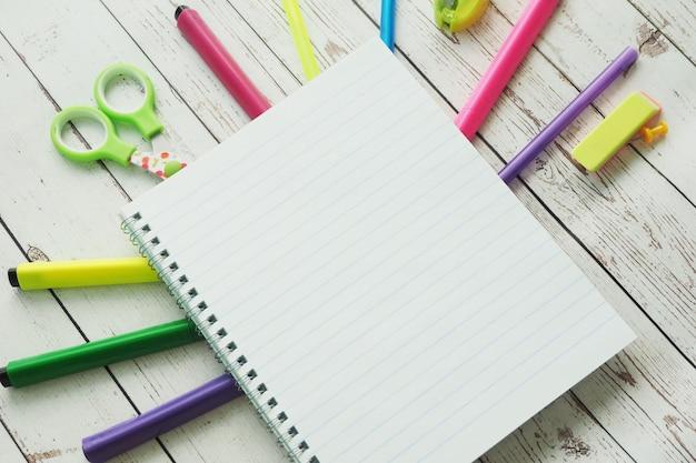 Un cahier ouvert, des marqueurs de couleurs vives, des stylos, un taille-crayon, une gomme, des ciseaux, des autocollants et de l'argile sur un fond en bois.