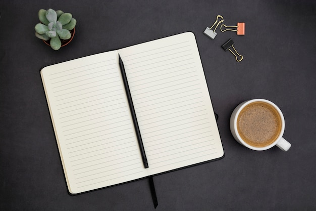 Cahier ouvert avec page vide et tasse de café. plateau de table, espace de travail sur fond sombre. mise à plat créative.