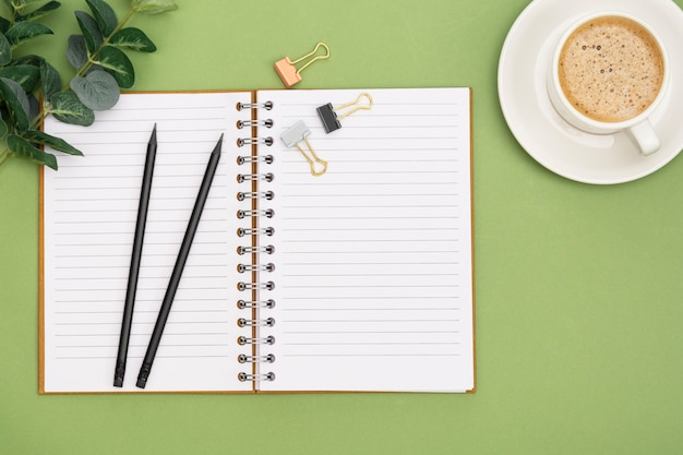 Cahier ouvert avec page vide et tasse de café. plateau de table, espace de travail sur fond vert. mise à plat créative.