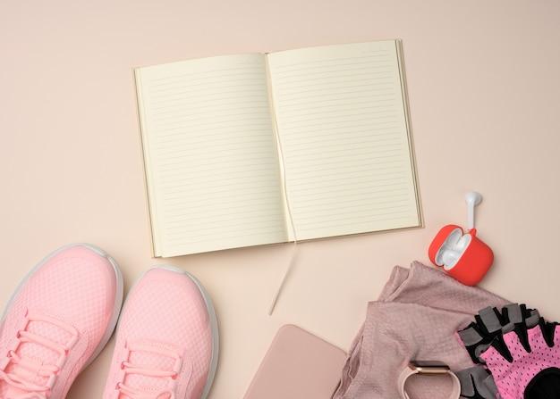 Cahier ouvert avec pages blanches, baskets roses et gadgets intelligents sur une surface beige. endroit pour enregistrer les objectifs et les réalisations, le calendrier, la pose à plat