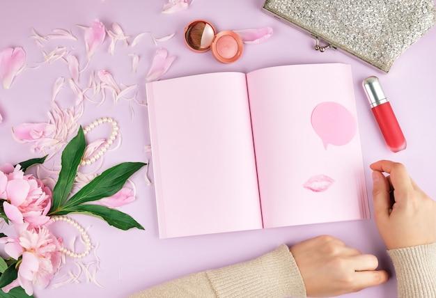 Cahier ouvert avec des pages vierges roses, un bouquet de pivoines, du rouge à lèvres et une pochette argentée