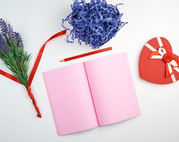 Cahier ouvert avec des pages vierges roses, un crayon rouge en bois et un bouquet de lavandes