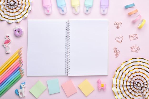 Un cahier ouvert parmi les fournitures scolaires aux couleurs pastel sur fond rose clair, une place pour le texte. arrière-plan avec des fournitures de bureau. retour à l'école. disposition plate, vue de dessus, un endroit pour copier.