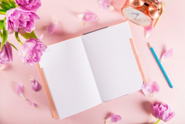 Cahier ouvert pour écrire des rêves et des idées avec des fleurs à proximité