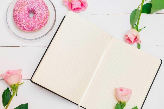Cahier ouvert avec roses roses pastel et beignet glacé rose