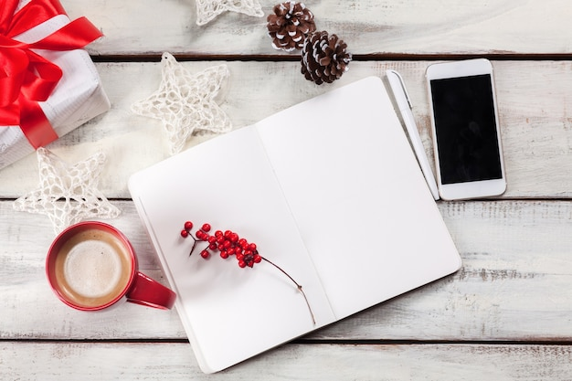 Le cahier ouvert sur la table en bois avec un téléphone et des décorations de noël.