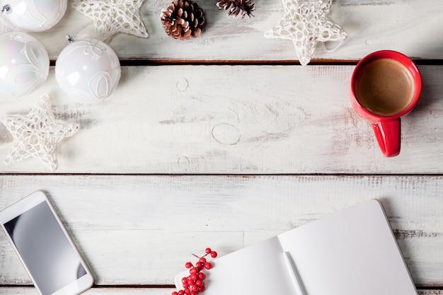 Le cahier ouvert sur la table en bois avec un téléphone
