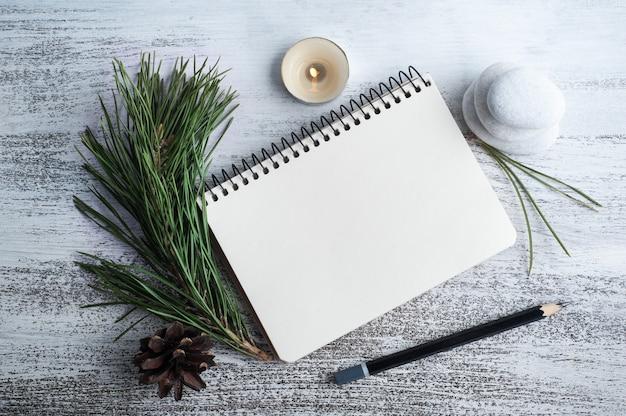 Cahier ouvert vide, pin et fleurs sèches sur fond rustique. carte de voeux avec espace de copie pour votre texte