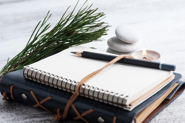 Cahier ouvert vide, pin et fleurs sèches sur table rustique.