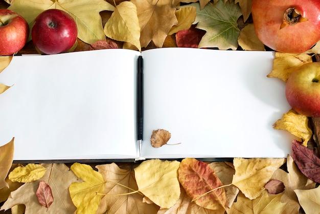 Cahier ouvert vierge avec stylo pour écrire. liste de choses à faire. automne automne backdround avec fruits et feuilles, mise à plat.