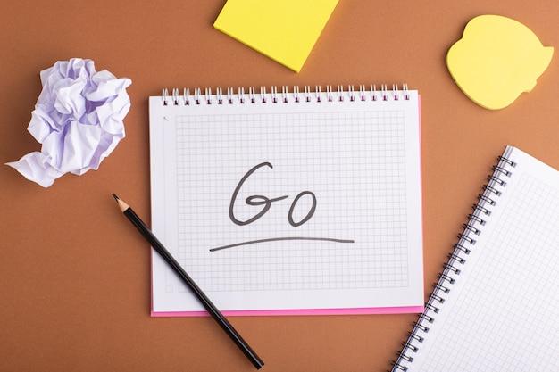 Cahier ouvert vue de dessus avec des autocollants et un crayon sur une surface brune