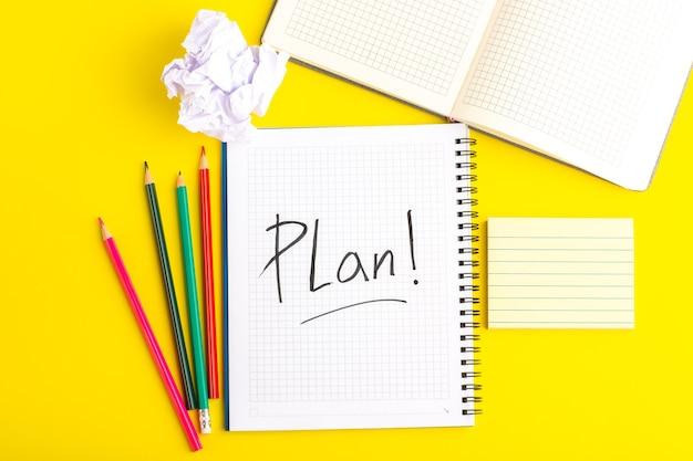 Cahier ouvert vue de dessus avec des crayons colorés sur un bureau jaune