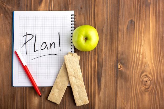 Cahier ouvert vue de dessus avec stylo cracker et pomme verte sur le sol brun