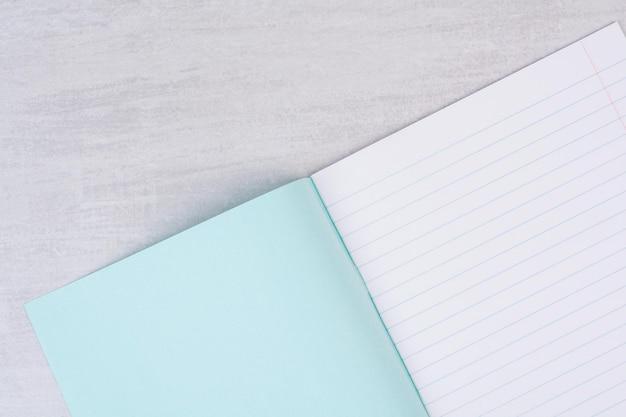 Cahier ouvert vue de dessus sur tableau blanc.