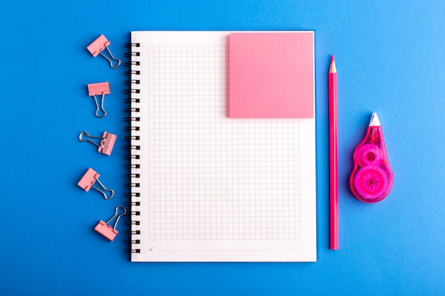 Cahier ouvert vue de face avec autocollant rose sur le bureau bleu