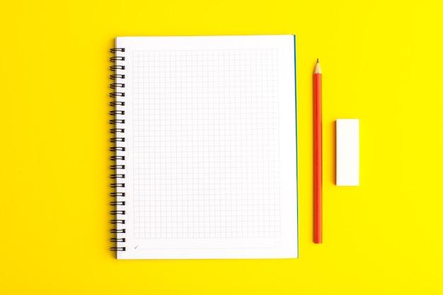 Cahier ouvert vue de face avec un crayon sur une surface jaune
