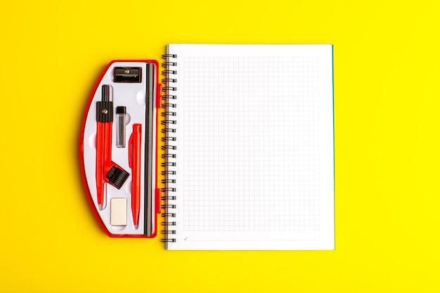 Cahier ouvert vue de face sur la surface jaune