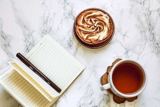 Cahier ouvert avec zone vierge, stylo et une tasse de thé noir sur une table en marbre blanc le matin.