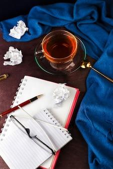 Cahier avec page blanche, papier à l'étroit, stylo, verres et tasse de thé