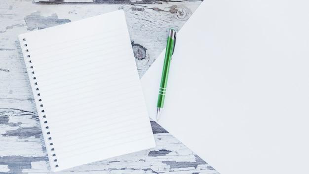 Cahier et papier sur un bureau minable en bois