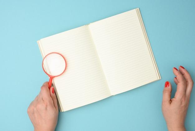 Cahier en papier avec des feuilles blanches vierges et une loupe rouge sur fond bleu