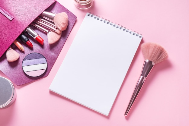 Cahier de papier à plat sur une maquette de table cosmétique rose