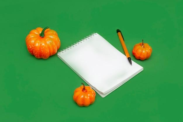 Un cahier en papier, un stylo à bille et des citrouilles oranges sur fond vert. vue de dessus. espace de copie. bloc-notes pour écrire les listes d'automne