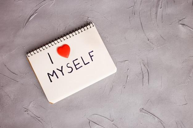 Un cahier avec une phrase écrite: je m'aime. concept de m'accepter.