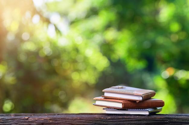 Cahier placé sur un bois avec lumière du soleil bokeh