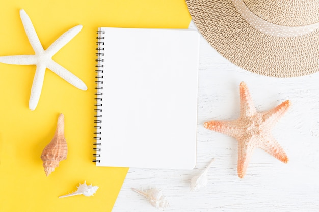 Cahier plat avec blanc et coquillage pour les vacances d'été sur papier jaune sur bois blanc