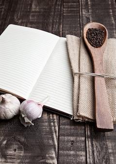 Cahier avec poivre sur cuillère et torchon sur planche de bois