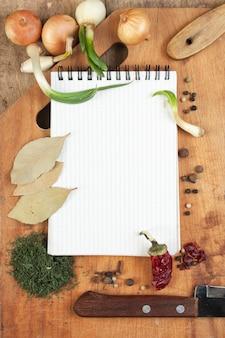 Cahier pour cuisiner des recettes et des épices sur une table en bois