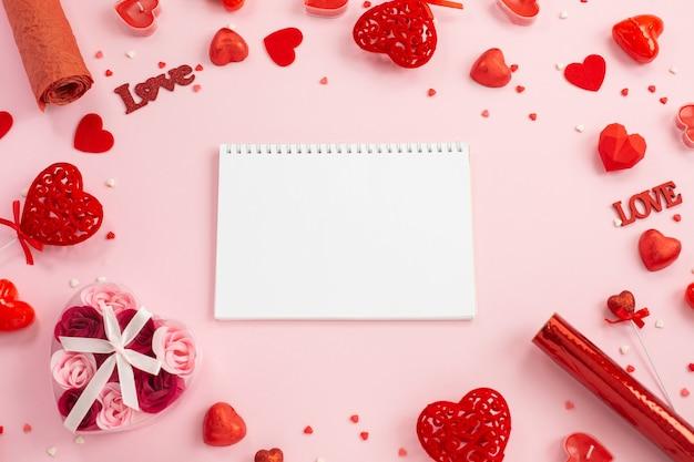 Cahier pour écrire avec des coeurs rouges, des cadeaux et des bougies.